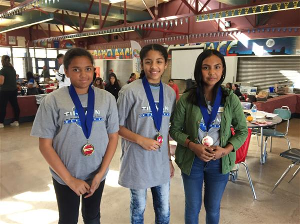 Image of 3 middle school students displaying their medals