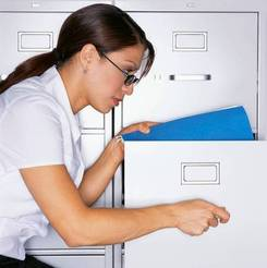 Staff member removing file folder from cabinet