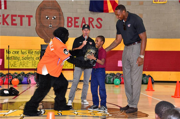 Phoenix Suns Gorilla giving student a backpack