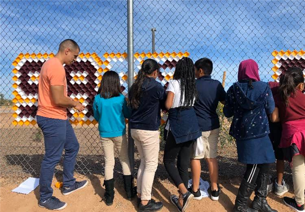 students and Desert Financial staff installing fence decoration