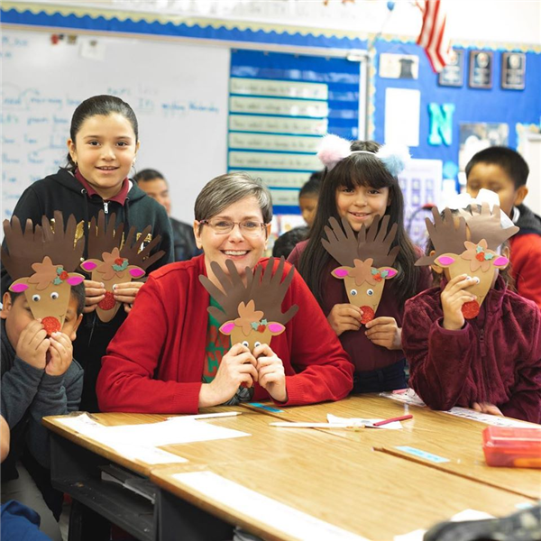 Desert Financial employee with students holding reindeer crafts