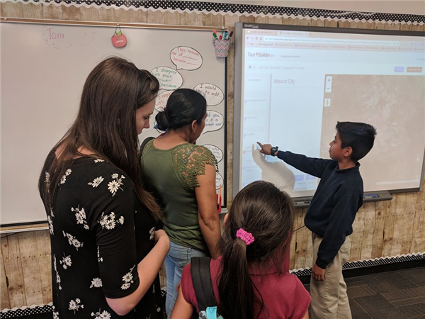 Student showing parents a project on the board